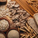 A table featuring a variety of whole grains including bread, pasta, and crackers.