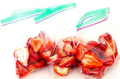 three plastic bags full of sliced strawberries
